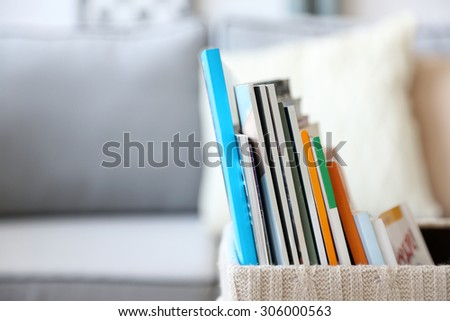 Magazines in basket in living room, close up