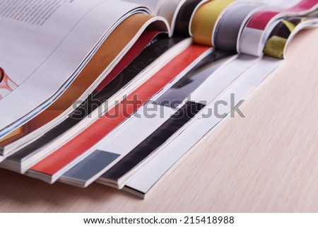 Magazines on wooden table close up - stock photo