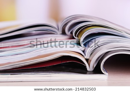 Magazines on wooden table on bright background