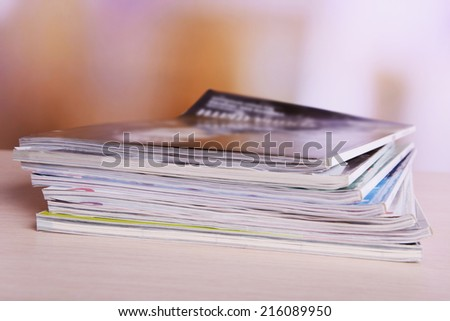 Magazines on wooden table on bright background - stock photo