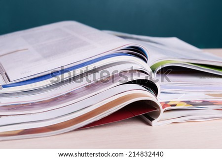 Magazines on wooden table on dark background - stock photo