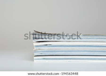 Magazines stacked in a pile isolated on white  - stock photo