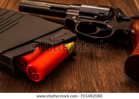 Magazines with red cartridges 12 gauge and revolver on the wooden table. Close up view - stock photo