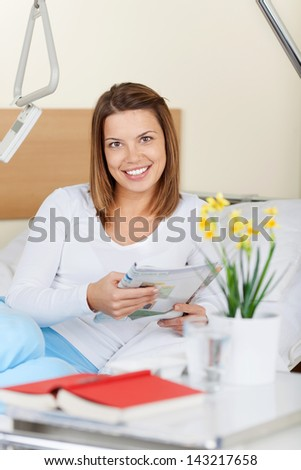 mage of a happy young female patient reading a magazine. Smiling for the camera. - stock photo