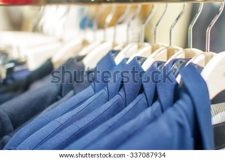 mage stylish jackets hanging on the rack in the storec - stock photo