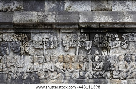 MAGELANG, INDONESIA - FEBRUARY 2, 2011: Ancient stone carving of worshippers meditating under Bodhi trees on the walls of Borobudur Temple. Borobudur Buddhist Temple is a UNESCO world heritage site.