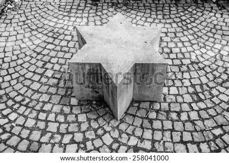 Magen David (star of David) on the cobblestone pavement  in Bonn, Germany (Black ) - stock photo