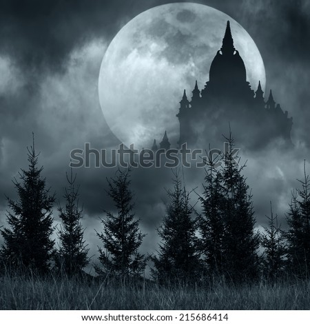 Magic castle silhouette over full moon at mysterious night. Fantasy background with pine tree forest under dramatic cloudy sky  - stock photo