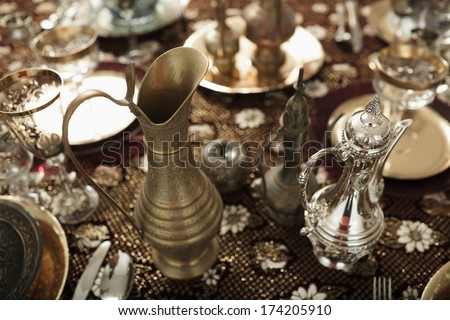 Magic dining. Decorated with antique jugs and bowls table looks like coming straight out of Aladdin store. - stock photo