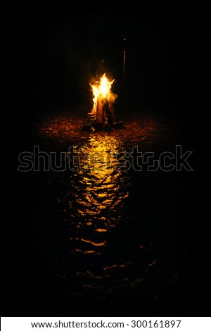 magic fire in the mountain river on the rocks at night. photo framed wholly in black