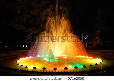 Magic fountain with colorful illuminations at night. - stock photo