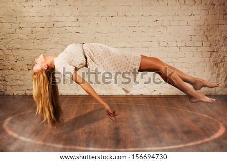 Magic moment - girl levitates on a brick wall background - stock photo