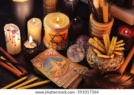 Magic objects, candles and the tarot cards in candle light.  Fortune telling seance or black magic ritual. Scary still life with occult and esoteric symbols. Halloween or divination rite - stock photo