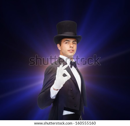 magic, performance, circus, show concept - magician in top hat showing trick