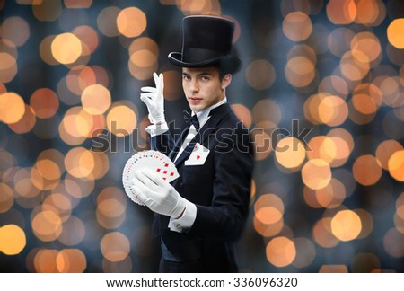 magic, performance, gambling, casino, people and show concept - magician in top hat showing trick with playing cards over nigh lights background - stock photo