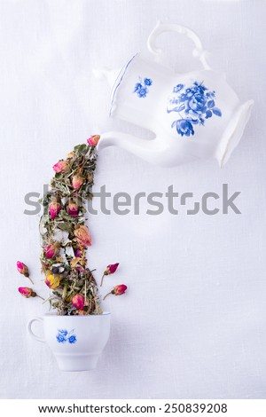 Magic porcelain white with blue teapot pouring dry herbs and roses tea in the cup, Mad Hatter tea party - stock photo