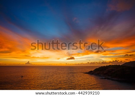 Magic sunset view from high point. Sea landscape with silhouette of island and colorfully cloudy sky. Location: Phromtep Cape Phuket Thailand.