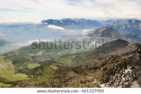 Magic view of the peaks of the Alps. Panorama from the top of the Schafberg with the Mondsee lake and green fields below and snow-capped peaks under the blue sky with clouds, St. Wolfgang Austria