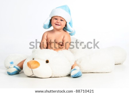 Magic winter: cute little boy sitting on a white teddy bear - stock photo