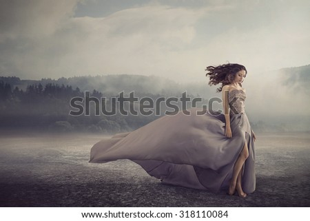 Magical brunette lady on a foggy field - stock photo