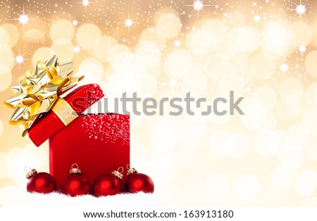 Magical Christmas Gift and Red Baubles With De-focused Background With Copy Space