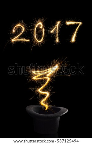 Magical new year. Magical fireworks from black top hat forming 2017 and abstract light lines isolated on black background. Happy new year background.