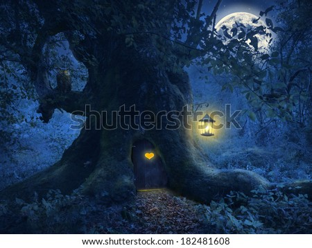 Magical night with a little home in the trunk of an ancient tree in the enchanted forest. - stock photo