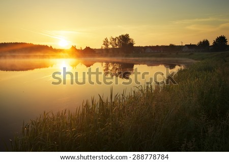 Magical sunset over the lake in the village. Composition of Nature  - stock photo