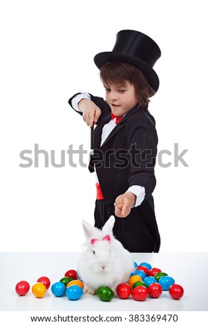 Magician boy doing an easter trick - with dyed eggs and white rabbit - stock photo