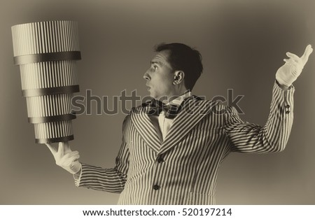 Magician conjuring tricks with the stacked gift boxes. Holiday shopping concept