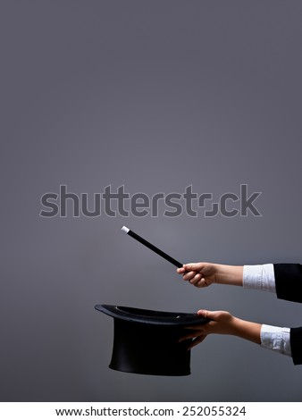 Magician hands holding hat and magic wand on gray background - with lots of copy space - stock photo