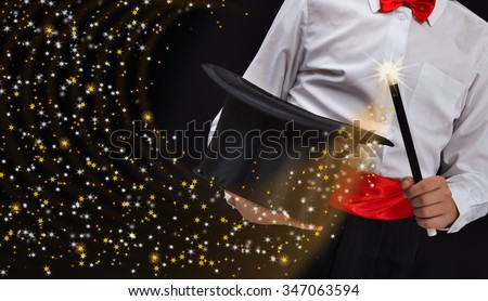 Magician hands with magic wand conjuring sparkling stars stream - copy space - stock photo