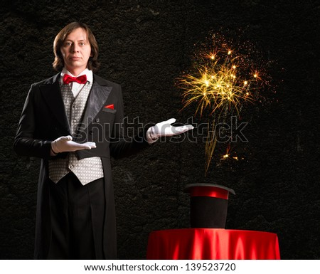 magician makes passes at the cylinder, the cylinder produces magic - stock photo