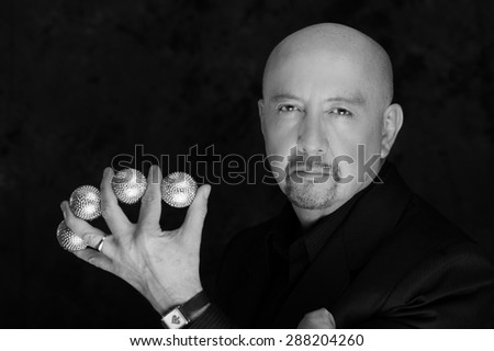 Magician man posing with five balls between fingers black and white edition - stock photo