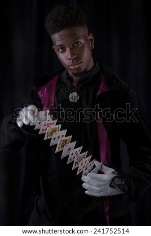 Magician performing on a stage with cards - stock photo