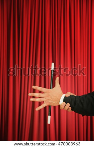 Magician performing simple trick with magic wand on stage