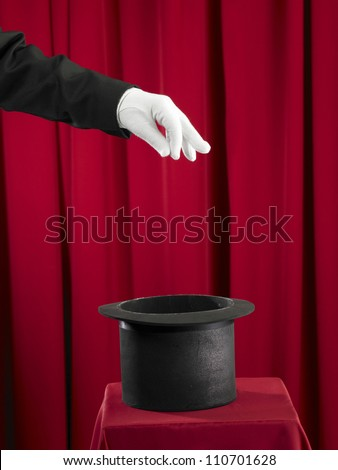 Magician picking some thing from top hat - stock photo