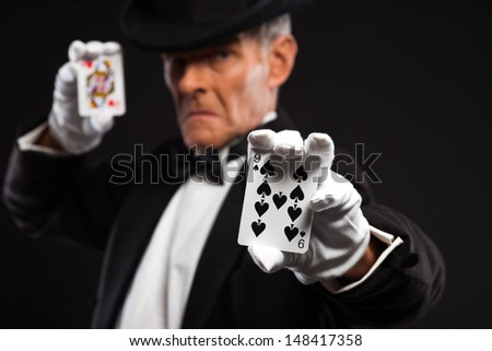 Magician with black suit and hat holding set of cards. Studio shot against black. - stock photo