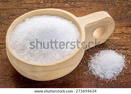 Magnesium sulfate (Epsom salts) in a rustic wooden scoop - relaxing bath concept - stock photo