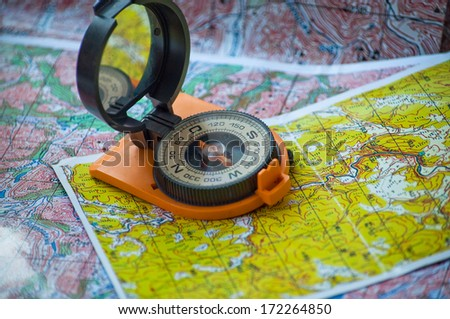 Magnetic compass in a red-black housing, equipped with a mirror, is on topographic maps. - stock photo