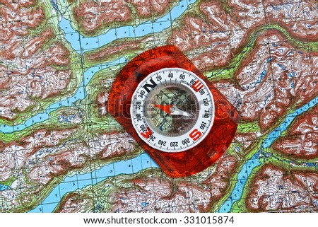 Magnetic compass is located on a topographic map. Navigation: a compass and a map. - stock photo