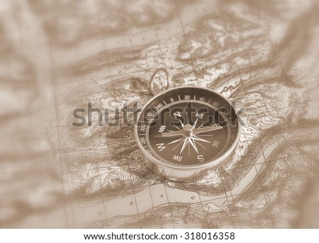 Magnetic compass is located on a topographic map. Orienteering in the wilderness - stock photo