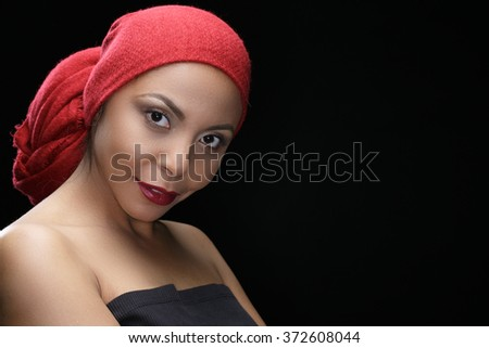 Magnetic ethnicity. Beauty portrait of a gorgeous African woman wearing red headscarf looking to the camera smiling
