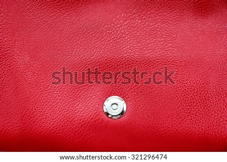 Magnetic iron stud on red artificial leather bag.