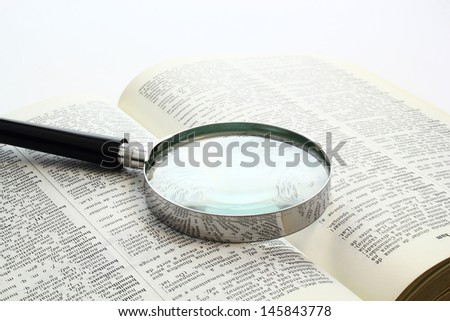 Magnification glass over a opened book - stock photo