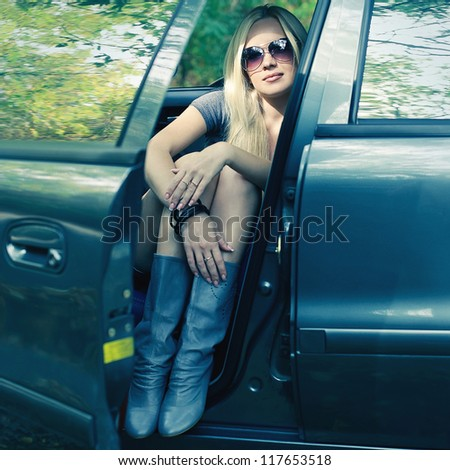 magnificent blonde driver girl with sunglasses sitting in blue colored car. outdoor shot - stock photo