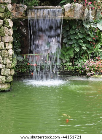 Magnificent decorative waterfalls with gold small fishes in tropical park