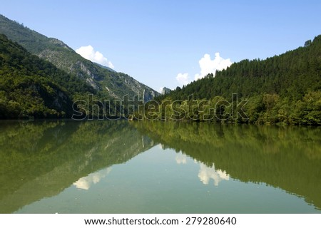 Magnificent Drina river at Bosnia and Herzegovina surrounded with mountains, dramatic sky and water reflection - stock photo