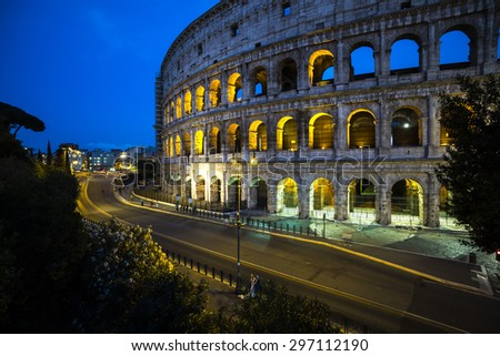Magnificent evening Coliseum or Amphitheatrum Flavium with bright illumination on blue sky background, Rome, Italy