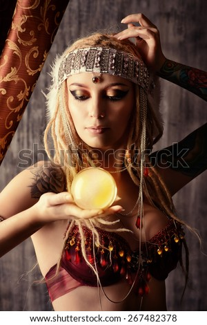 Magnificent fortune teller holding crystal ball. Divination. Magic. Halloween. - stock photo